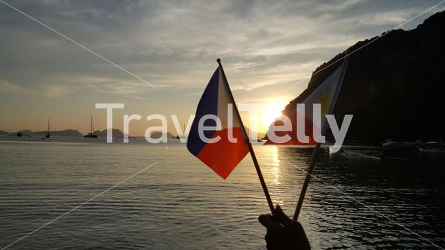 Sunset with national flag in hand at El Nido beach, Palawan, Philipinnes