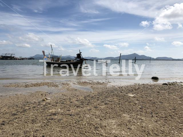 Long-tail boat during low tide on Koh Mook island in Thailand