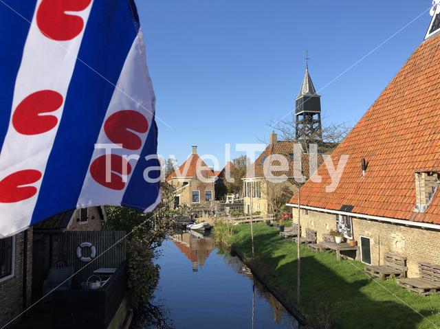 Frisian flag at a canal in Hindeloopen during autumn in Friesland, The Netherlands