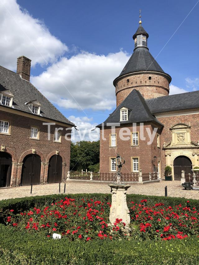Statue and flowers at the Wasserburg Anholt castle in Munsterland, Germany