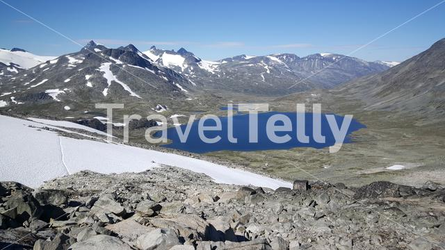 Crater lake and mountains with snow in Jotunheimen National Park Norway