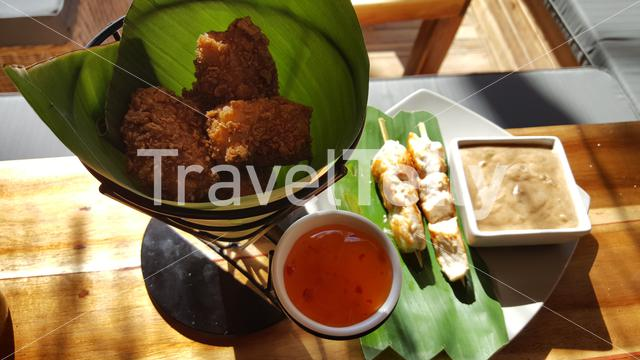 Chicken nuggets and sate with peanut sauce in tropical style