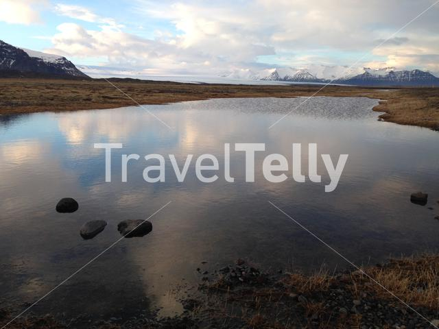 Iceland landscape with snowy mountain reflection in a pond