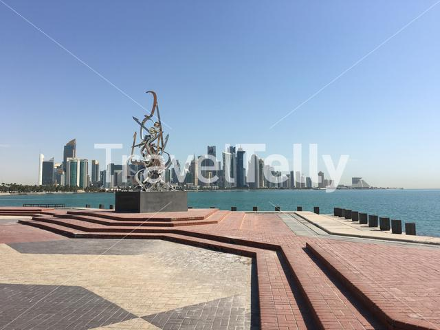 The Corniche with a statue and the Doha skyline in Qatar