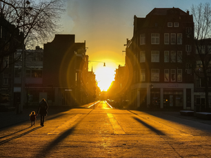 Mother and daughter walking during sunrise at Haarlemmerplein in Amsterdam The Netherlands