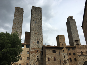 Towers of San Gimignano against a dark and cloudy sky in Tuscany, Italy.