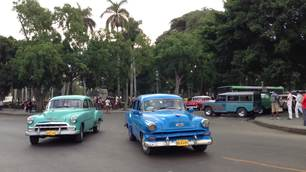 following a blue and green classic old car in Havana, Cuba