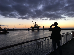 Guy takes a picture during sunrise in the harbour of Las Palmas