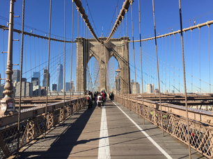 People walking at the Brooklyn Bridge with the Freedom tower and Manhattan at the background in New York City