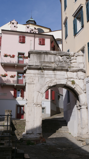 Old roman gate in a narrow street of Trieste, Italy
