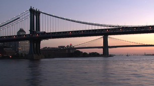 Manhattan Bridge and the Brooklyn Bridge in New York during sunset from a ferry at the East River