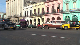 Classic cars driving through the streets with colourful houses in Havana Cuba