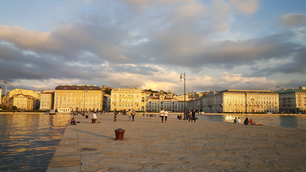 People at the pier of Trieste at sunset