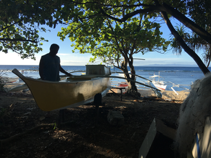 Fisherman working on his Catamaran Boat at the beach of Balicasag Island in Bohol the Philippines