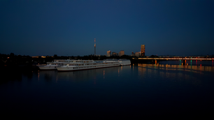 Railway at Donau river with Millennium Tower in Vienna at night