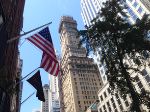 American flag with skyscrapers in the streets of New York City
