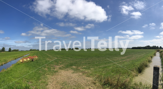 Panorama from farmland with a hay machine on farmland in Friesland The Netherlands