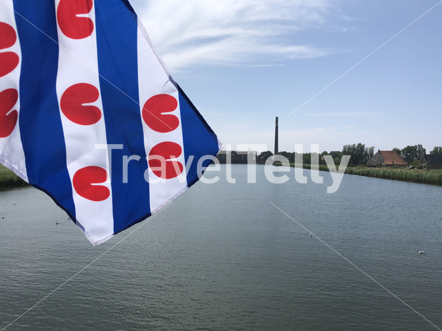 Frisian flag with in the background the wouda pumping station in Lemmer, Friesland The Netherlands