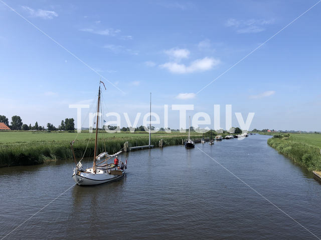 Sailboat sailing towards the bridge and the langweerder wielen lake in Langweer, Friesland The Netherlands