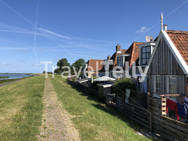 Houses next to a dyke in Makkum, Friesland The Netherlands