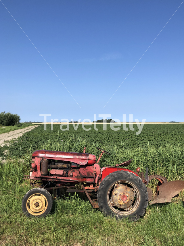 Tractor at farmland in Sint Annaparochie in Friesland The Netherlands